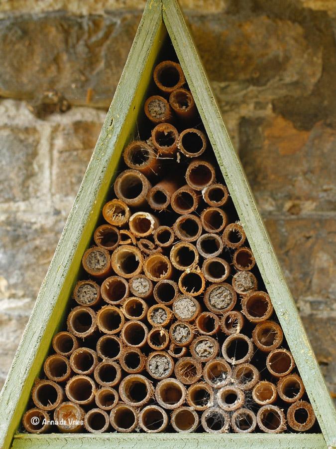 Bijenhotel met verschillende dicht gemetselde bamboepijpjes.